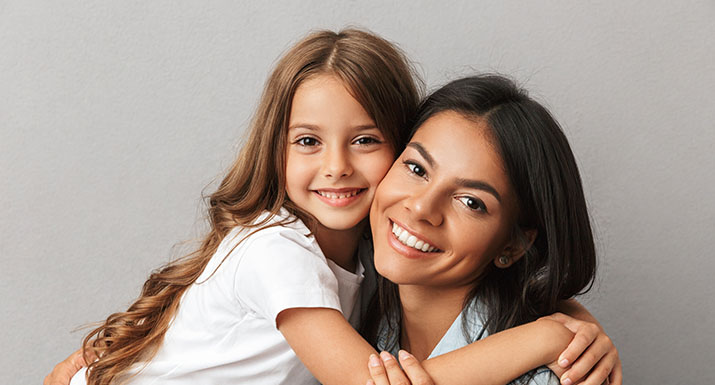 Imagen madre e hija sonriendo para introducir post ¿Qué es y cómo tratar la anquilosis dental?