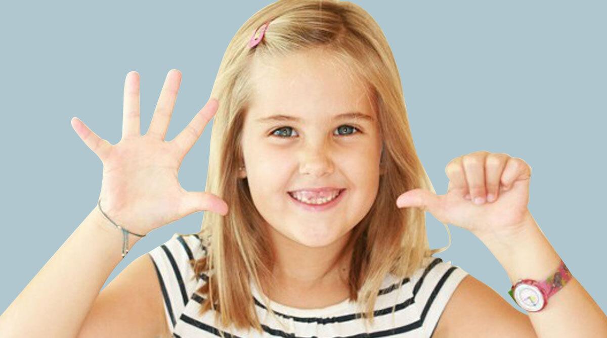 Primer pla d'una nena mostrant amb els seus dits que l'ortodòncia en nens és recomanable als 6 anys